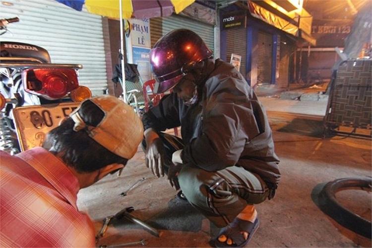 2h sáng, trên đường Đinh Bộ Lĩnh, người đàn ông này ăn mặc kín đáo nhất có thể trong lúc chờ sửa xe.