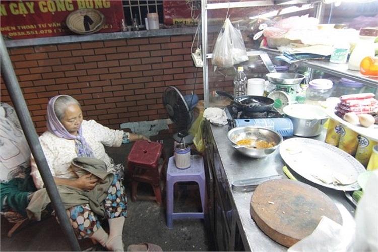 Bà Nguyễn Thị Tha (60 tuổi) - bán bánh mì đêm gần bến xe miền Đông. Bà Tha cho biết: 'Những đêm trước tôi chỉ mặc 2 cái áo, có khi còn bật cả quạt. Nhưng độ này trời lạnh quá nên mặc đến 3 áo và quấn thêm khăn'.