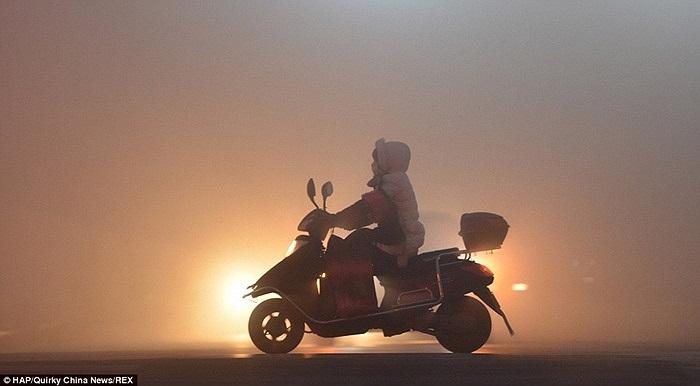 Người phụ nữ đi xe máy trong sương độc ở Phụ Dương, tỉnh An Huy