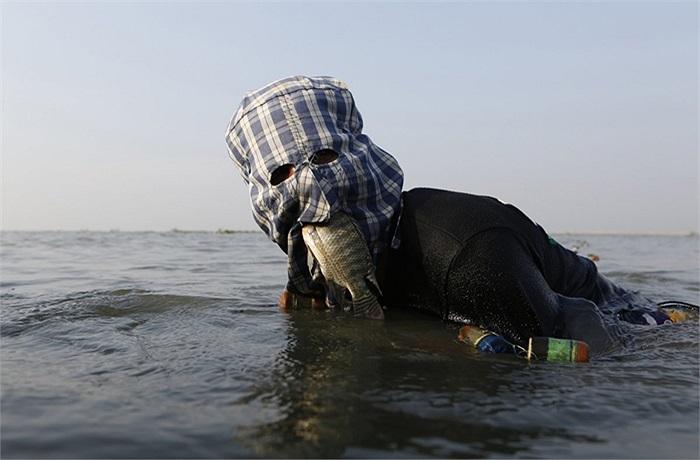 Ngư dân Philippines dùng miệng giữ cá vừa bắt được ở Manila