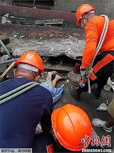 Nhân viên cứu hộ đưa thi thể nạn nhân ra khỏi đống đổ nát
