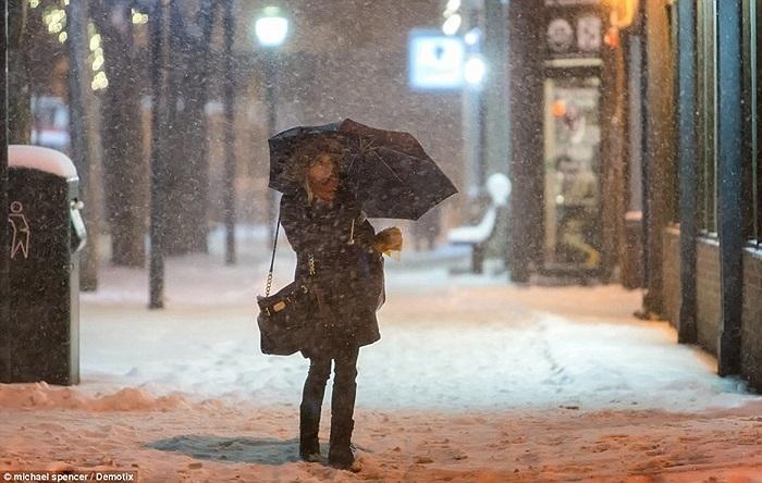 Cô gái và chiếc ô mỏng manh chống tuyết trên đường phố Boston