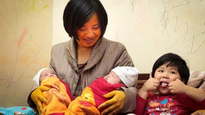Từ trái qua phải: Bé Hồ Sĩ Hoàng Hải (em) và bé Hồ Sĩ Hoàng Đức (anh) trong vòng tay của chị Hoàng Thị Kim Dung, bên cạnh là bé Hồ Hoàng Hải Bình, con gái lớn của chị Dung - Ảnh: Nguyễn Khánh