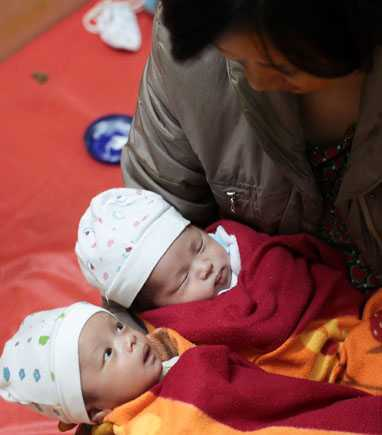 Hai bé Đức và Hải bình yên trong vòng tay của mẹ Hoàng Thị Kim Dung - Ảnh: Nguyễn Khánh