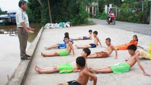 Thầy Lê Trung Sứng hướng dẫn học trò tập bơi - Ảnh: Trần Đình Phượng