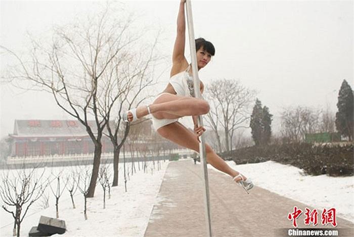 Nữ vận động viên múa cột trên nền tuyết trắng xóa