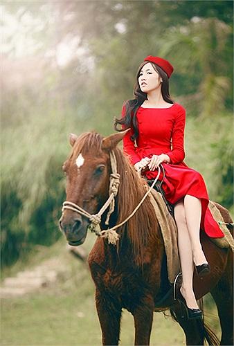 Tú Anh cưỡi ngựa tạo dáng giữa cánh đồng.