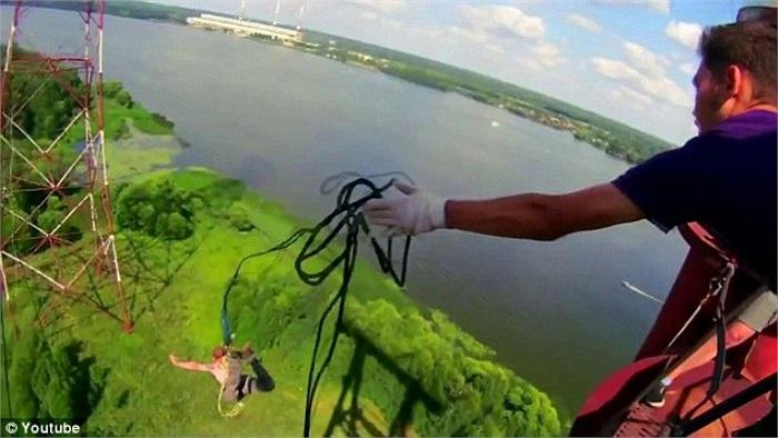 Một thanh niên vừa nhảy xuống dưới với sự hỗ trợ của đồng nghiệp để chắc rằng sợi dây không bị vướng.