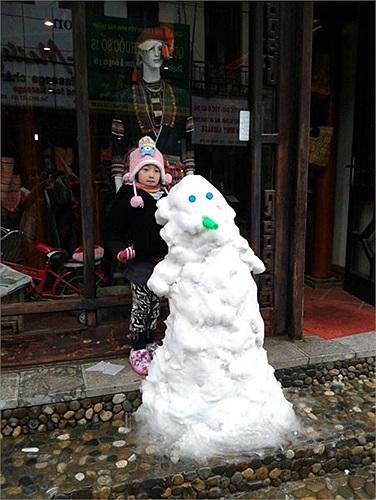 Một em bé cố tranh thủ ngắm tượng tuyết.