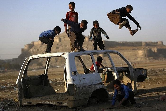 Những cậu bé chơi đùa trên một chiếc xe bị phá hủy ở Kabul