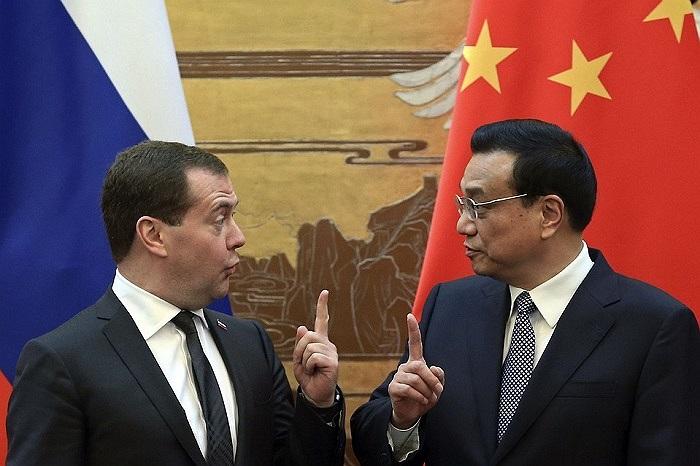 Thủ tướng Trung Quốc Lý Khắc Cường và người đồng cấp Nga Dmitry Medvedev cùng có một cử chỉ trong lễ ký kết tại Bắc Kinh ngày 22/10
