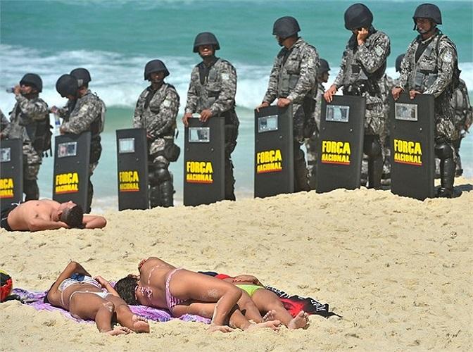 Người dân tắm nắng trên bãi biển trong khi lực lượng an ninh quốc gia Brazil đang canh giữ trước một khách sạn nơi cơ quan dầu khí quốc gia tổ chức một cuộc họp