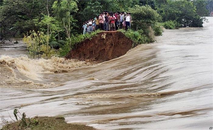 Người dân một ngôi làng Ấn Độ đứng bên bờ sông bị sạt lở do cơn bão Phailin