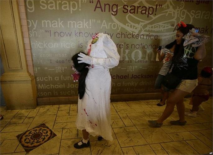 Cô dâu không đầu bé bỏng cầm đầu của mình đi lang thang trên đường phố, thực ra đây là một bé gái trong trang phục Halloween đi xin kẹo ở Manila, Philippines