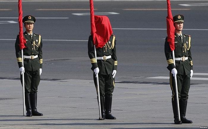 Lá cờ che khuất mặt một binh sĩ đội dàn chào danh dự trong lễ đón mừng Thủ tướng Mông Cổ Norovyn Altankhuyag bên ngoài Đại Sảnh Đường Nhân Dân ở Bắc Kinh, Trung Quốc