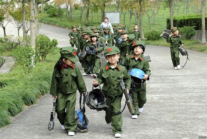 Trẻ em Trung Quốc mặc áo lính, cầm súng đồ chơi