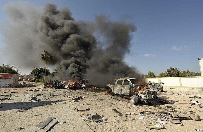 Chiếc xe cháy sau khi quả bom trong xe phát nổ gần một trường học nơi có lớp tập huấn về bầu cử hội đồng thành phố, tại Benghazi, Libya