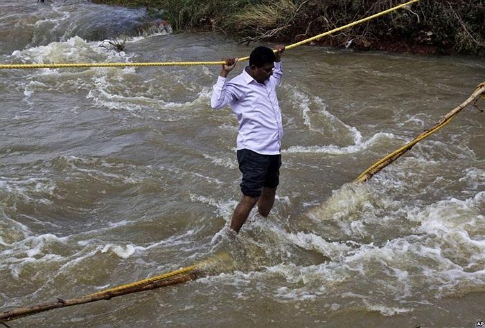 Người dân địa phương băng qua nước lũ bằng cầu dây tại làng Agastinuagaon, quận Ganjam, bang Oriss của Ấn Độ