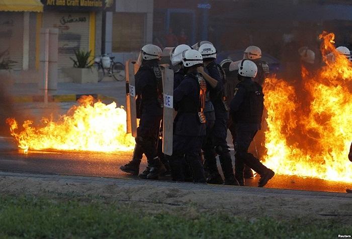 Cảnh sát chống bạo động dùng khiên đỡ bom xăng trong biểu tình ở Manama, Bahrain
