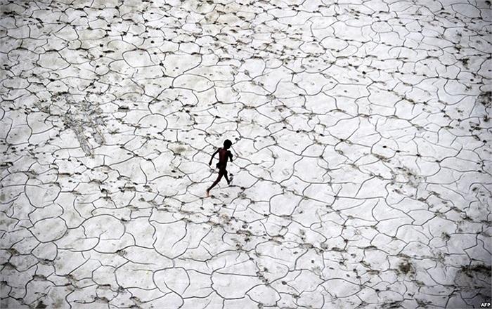 Em bé Ấn Độ chơi tại một lòng sông khô cạn sau khi nước lũ rút đi ở Allahabad