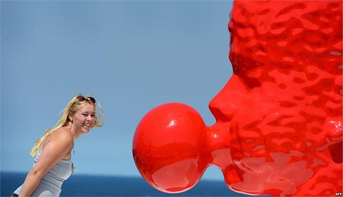 Du khách đứng chụp hình bên bức điêu khắc chiếc đầu thổi bong bóng cao 2m màu đỏ trong cuộc triển lãm ờ Sydney, Australia