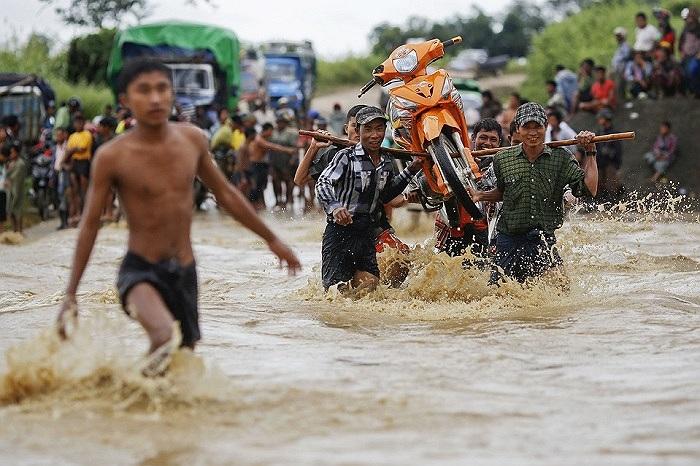 Sáu người cùng khiêng một chiếc xe máy lội qua nước lũ trên đường phố Myanmar