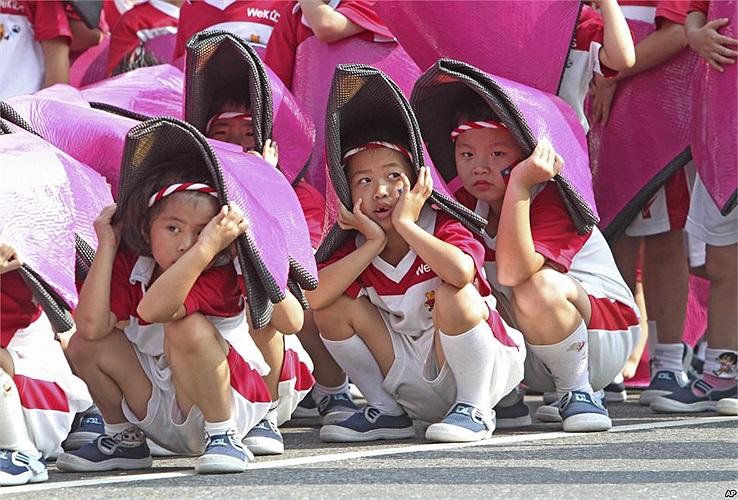 Trẻ em Đài Loan ngồi chịu nắng trong buổi diễn tập để kỷ niệm 'Ngày Quốc gia' (10/10 hàng năm) tại văn phòng chính phủ ở Đài Bắc
