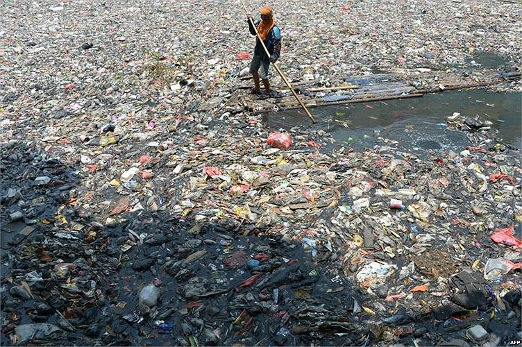 Một người dân Indonesia đang vớt rác tại một dòng sông bị ô nhiễm nặng ở Jakarta