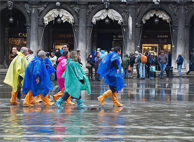 Du khách mặc áo mưa nhiều màu, đeo ủng, đi bộ trên quảng trường Saint Mark, Venice, Italia, những con phố tại đây đều bị ngập do thủy triều dâng cao