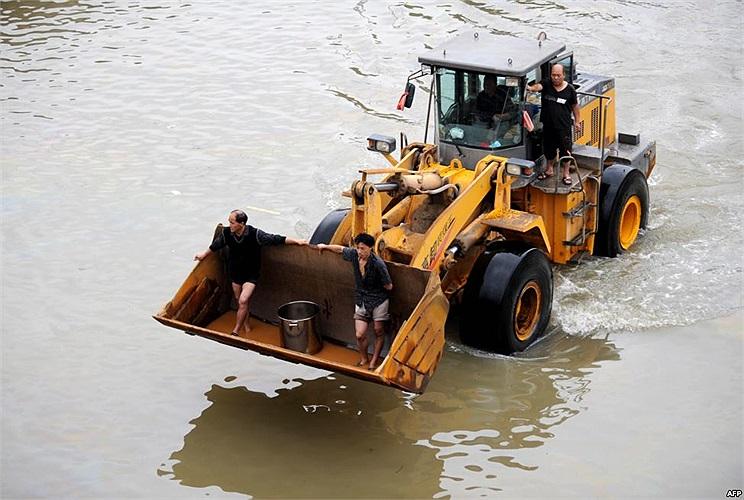 Người dân Chiết Giang, Trung Quốc di chuyển bằng xe ủi trên những con phố ngập nước lũ