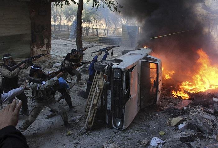 Binh lính Syria nấp sau một chiếc xe bị phá hủy trong một cuộc đọ súng với lực lượng trung thành với tổng thống Bashar al-Assad