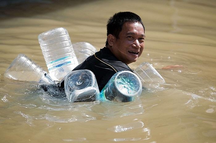 Một người đàn ông ở Kabin Buri, Thái Lan đeo những lọ nhựa lội trong nước lũ