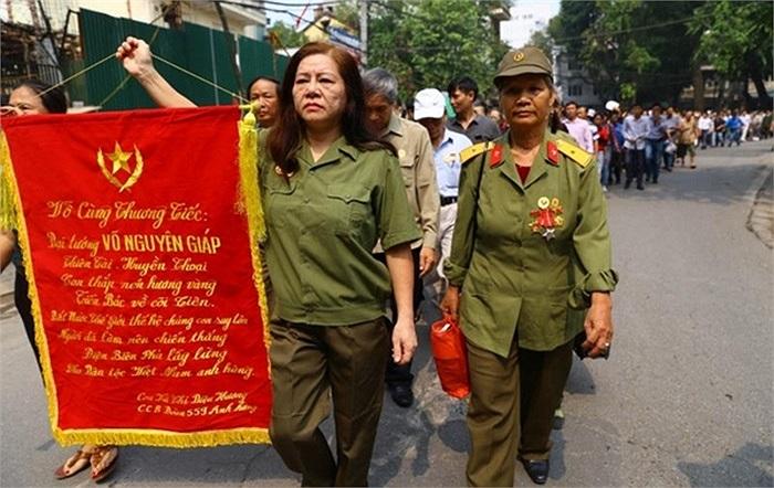 Nữ cựu chiến binh Vũ Thị Diệu Hương cầm lá cờ ca ngợi Đại tướng để tỏ lòng tôn kính khi tới viếng Người ở Nhà tang lễ Quốc gia hôm 12/10