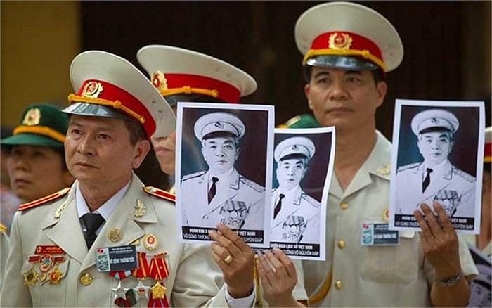 Các cựu chiến binh cầm chân dung Đại tướng xếp hàng vào viếng Người