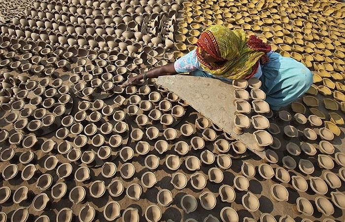 Người phụ nữ hong khô những chiếc đèn đất sẽ được dùng trong lễ hội ánh sáng Diwali ở Ấn Độ