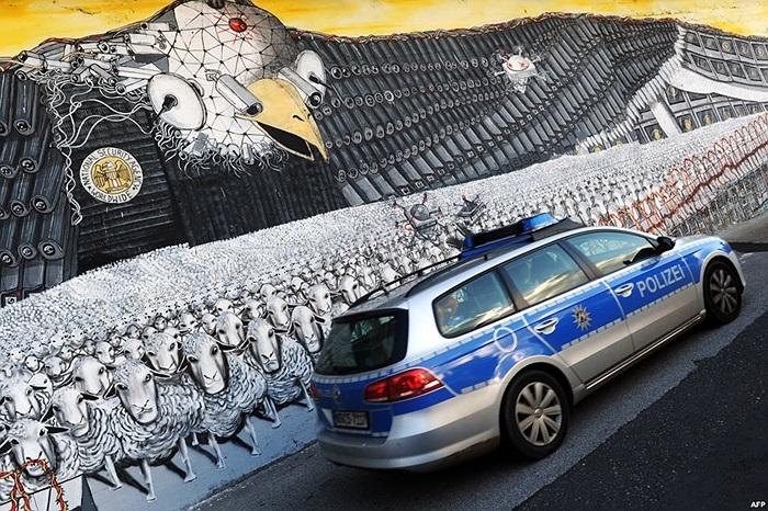 Xe tuần tra của cảnh sát Đức băng qua bức tường đầy những hình vẽ
