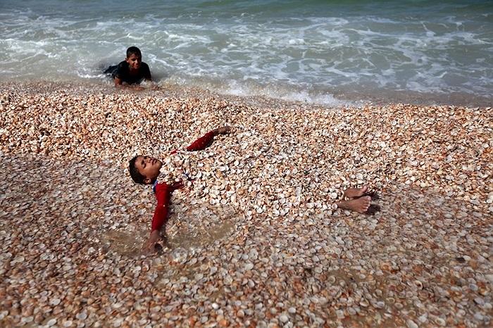 Hai cậu bé người Palestine chơi đùa trên bãi biển ở dải Gaza