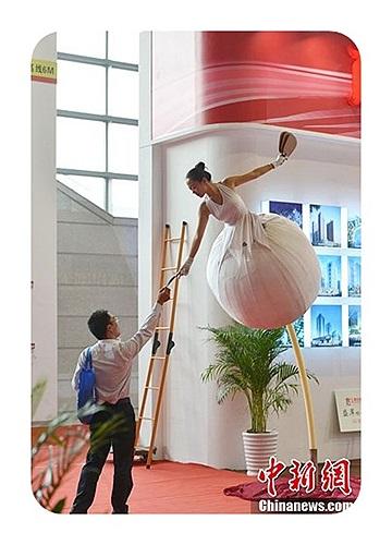Một cô gái khác đứng trong một quả bóng trên cao tặng khách hàng những chiếc quạt gấp tại một hội chợ nhà ở được tổ chức tại Vô Tích, tỉnh Giang Tô ngày 11/10.