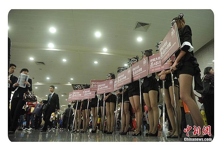 Những cô gái 'chân dài' trong bộ đồ ngắn cầm những tấm áp phích quảng cáo cho một công ty bất động sản tại hội chợ nhà ở được tổ chức tại Trùng Khánh, Trung Quốc vào ngày 17/10.