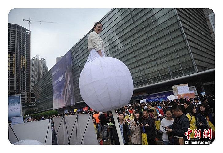 Một cô gái đứng trong một quả bóng trên cao để quảng cáo cho công ty bất động sản, thu hút sự chú ý của rất nhiều người xem tại hội chợ nhà ở được tổ chức tại Trùng Khánh vào ngày 17/10.