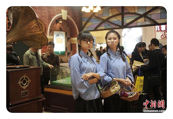 Những cô gái mặc đồng phục học sinh tặng hoa cho khách hàng tại một hội chợ nhà ở cũng được tổ chức tại Trùng Khánh.