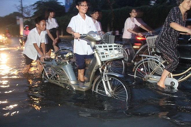 Các học sinh trường khác lội nước về nhà. Nước ngập sâu đến nửa mét, khiến xe đạp điện chết máy, hai học sinh này thay nhau đẩy xe.