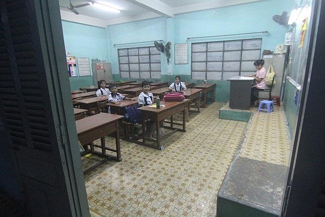Một lớp còn sáng đèn, giáo viên ở lại trông các em chờ phụ huynh tới đón.