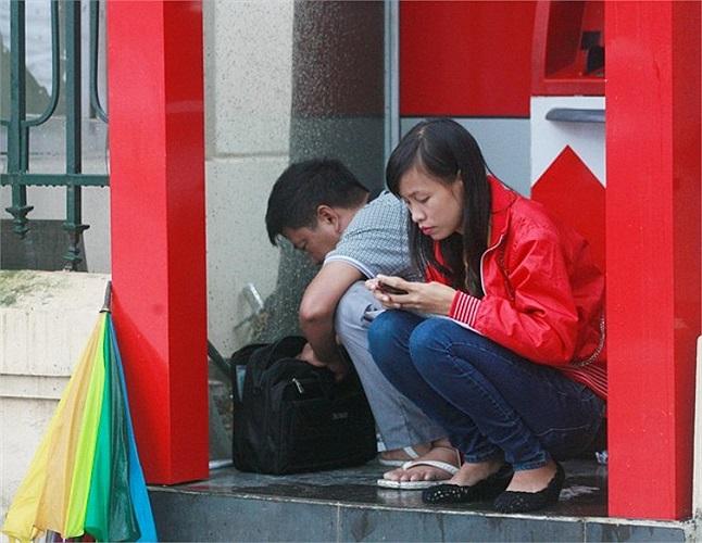 Một số người chui vào buồng ATM để tránh rét trên đường Trần Duy Hưng.