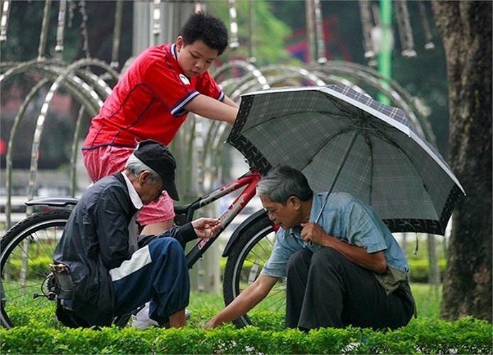 Đôi bạn già chơi cờ ở Hồ Tây che thêm chiếc ô để tránh gió.