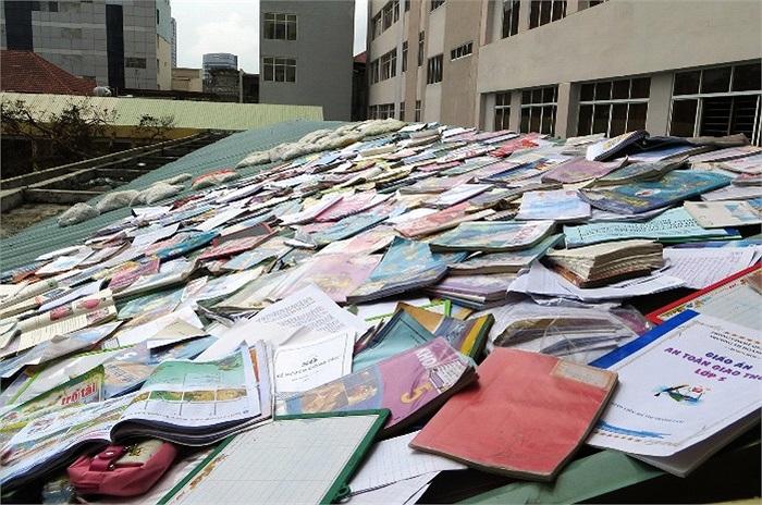 Sách vở học sinh bị ướt được giáo viên gom và phơi trên mái nhà.
