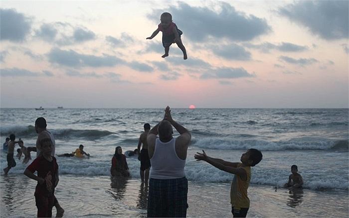 Một gia đình Palestine chơi đùa trên bãi biển ở Gaza dưới ánh hoàng hôn