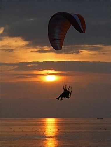 Người lái dù lượn tận hưởng những tia nắng cuối cùng trong ngày ở Heacham, tây Norfolk, Anh
