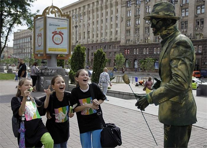 Các bé gái trêu đùa nghệ sĩ đường phố ở thủ đô Kyiv, Ukraina