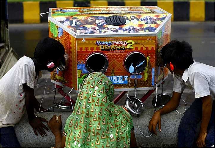 """Người phụ nữ và hai cậu bé đang xem trailer phim  """"Yamla Pagla Deewana 2"""" bằng một cái máy truyền thống"""